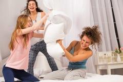 Девушки в кровати имея бой подушками в пижамах Стоковые Изображения