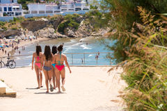 4 девушки в купальных костюмах идут к пляжу в Sitges, Барселоне, Catalunya, Испании Стоковая Фотография RF