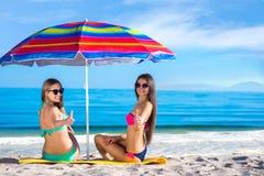 Девушки в купальниках на пляже под зонтиком Стоковое Изображение RF