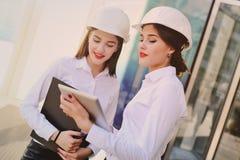 Девушки в одеждах дела и белых шлемах конструкции обсуждают бизнес-план или контракт Стоковое Изображение