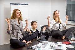 Девушки в офисе размышляя в положении лотоса Стоковое фото RF