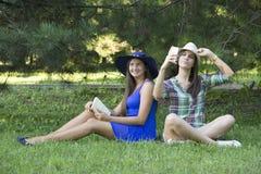 Девушки в парке с книгой и мобильным телефоном Стоковые Фотографии RF