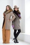 Девушки в пальто представляя на студии Стоковые Фотографии RF