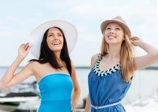 Девушки в платьях с шляпами на пляже Стоковое Изображение RF