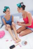 Девушки в роликах волос крася каждые другие ногти Стоковые Изображения