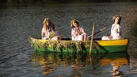 3 девушки в славянском национальном костюме в шлюпке плавая на реку Девушки в венках представляя и смеясь над весело видеоматериал