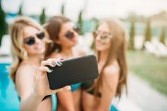3 девушки в солнечных очках объявления купальников делают selfie Стоковые Изображения RF