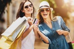 Девушки в солнечных очках с кредитной карточкой в их руке Стоковые Фотографии RF