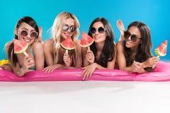 Девушки в солнечных очках держа арбуз соединяют пока лежащ на плавая тюфяке Стоковое Изображение