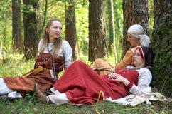 Девушки в старом русском национальном платье сидя в древесинах Стоковая Фотография RF