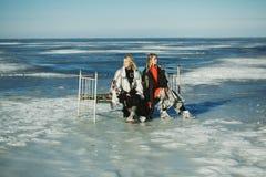 Девушки в старых одеждах сидят на кровати на льде замороженного Стоковая Фотография
