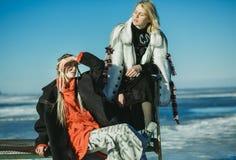 Девушки в старых одеждах сидят на кровати на льде замороженного Стоковые Фото
