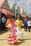 Девушки в фламенко одевают на ярмарке Севильи Стоковые Фото