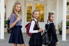 3 девушки в школьной форме с рюкзаками стоят на шагах Стоковые Фотографии RF