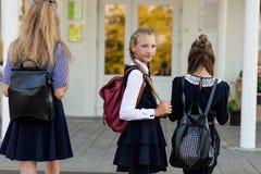 3 девушки в школьной форме с рюкзаками стоят на шагах Стоковая Фотография