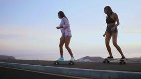 2 девушки девушки в шортах и тапки едут скейтборды на наклоне против красивого неба восходящего солнца сток-видео
