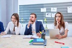 2 девушки, говоря на телефоне и работая за таблеткой, и взгляды человека в расстояние Стоковые Изображения