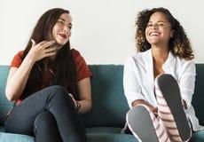 Девушки говоря совместно на кресле Стоковое Фото