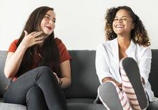 Девушки говоря совместно на кресле Стоковое Изображение
