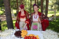 Девушки гостя встречи красивые в национальных русских костюмах, sundresses мантий с живой вышивкой - фольклорной группой колесо Стоковая Фотография RF