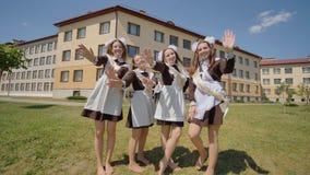 Девушки градуируют в школьных формах посылают поцелуй воздуха к камере Русские студент-выпускники празднуют последний учебный ден акции видеоматериалы