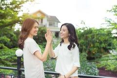 2 девушки давая 5 пока стоящ совместно outdoors Стоковые Фото