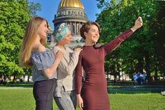 Девушки делают selfie на телефоне на предпосылке ` s Ca St Исаак Стоковая Фотография RF