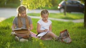 Девушки делая домашнюю работу в саде лета Они имеют много потеху получая знание видеоматериал