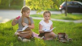 Девушки делая домашнюю работу в саде лета Они имеют много потеху получая знание сток-видео