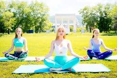 Девушки делая йогу в парке Стоковое фото RF