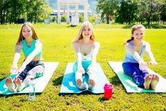 Девушки делая йогу в парке Стоковая Фотография RF
