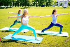Девушки делая йогу в парке Стоковая Фотография
