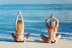2 девушки делая йогу представляют на береге карибского моря Стоковые Фото