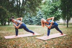2 девушки делая йогу outdoors Стоковое Фото