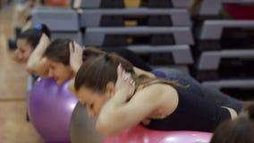 4 девушки делая спорт с шариками фитнеса в спортзале сток-видео