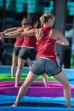 Девушки делая тренировки на плавая циновке фитнеса в открытом бассейне Стоковые Фотографии RF