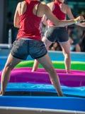 Девушки делая тренировки на плавая циновке фитнеса в открытом бассейне Стоковое фото RF