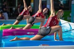 Девушки делая тренировки на плавая циновке фитнеса в открытом бассейне Стоковая Фотография RF