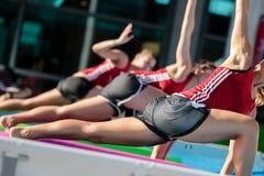 Девушки делая тренировки на плавая циновке фитнеса в открытом бассейне Стоковые Изображения