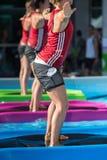 Девушки делая тренировки на плавая циновке фитнеса в открытом бассейне Стоковая Фотография