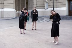 3 девушки делая фото с smartphone их девушки друга в черных платьях Стоковые Изображения RF