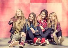 Девушки делая selfie outdoors пока сидящ на longboards Стоковые Изображения RF