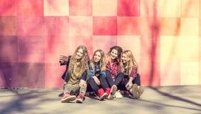 Девушки делая selfie outdoors пока сидящ на longboards Стоковая Фотография