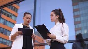 2 девушки дела обсуждают проект деятельности стоя на улице вверх по деловому центру 4K видеоматериал