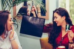 2 девушки деля их новые приобретения друг с другом стоковые фото