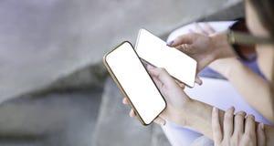 2 девушки держа мобильный умный телефон рядом друг с другом деля клиппирование предпосылки экрана модель-макета белое используя п стоковые фотографии rf