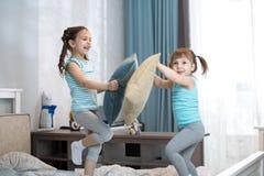 Девушки детей имеют потеху играя с подушками дома Стоковое Изображение RF