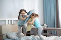 Девушки детей имеют потеху играя с подушками дома Стоковое фото RF
