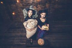 Девушки детей костюмируют ведьм с тыквами и обслуживаниями в Стоковые Фотографии RF