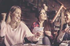 3 девушки дома играя карточки стоковое изображение rf